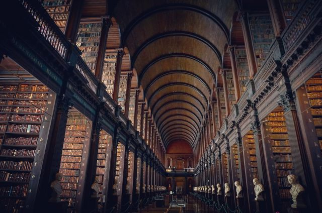 An ornate wood-panelled large library with an arching roof and row upon row of shelves.