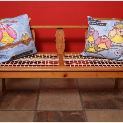 picture of an antique wooden bench with 2 pillows