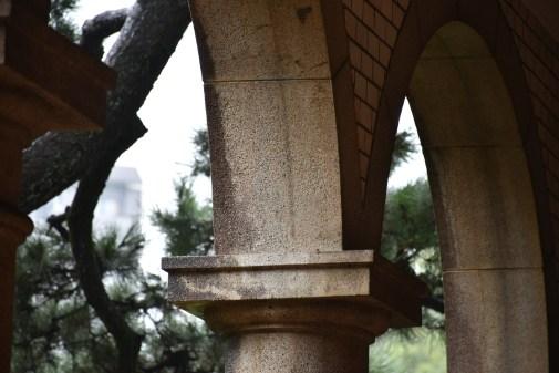 岡田さん。洋館のアーチを斜めから撮影。人でいう「頭」にあたる柱の装飾はしっかり中央に収め、アーチの一部は潔くカットしました。
