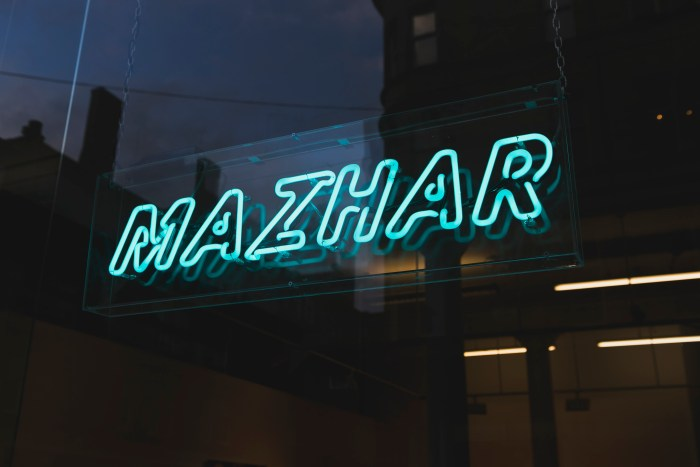 Dad (2018) 1000mm x 300mm - an artwork hung in the window which is made of Turquoise Neon tubing spelling the name MAZHAR and is encased in clear perspex / Photography by Eoin Carey