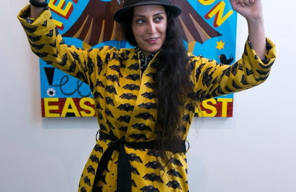 Rabiya Choudhry dressed in a black hat and yellow coat with repeating black spoder design. She is standing in front of a painting which has the text Rabiya Choudhry Presents TERRORVISION with further text at the bottom hidden by her body. She is looking to her left and raising both her arms in the air with her fists closed. This was taken at her exhibition COCO!NUTS! at Transmission Gallery By Eoin Carey.