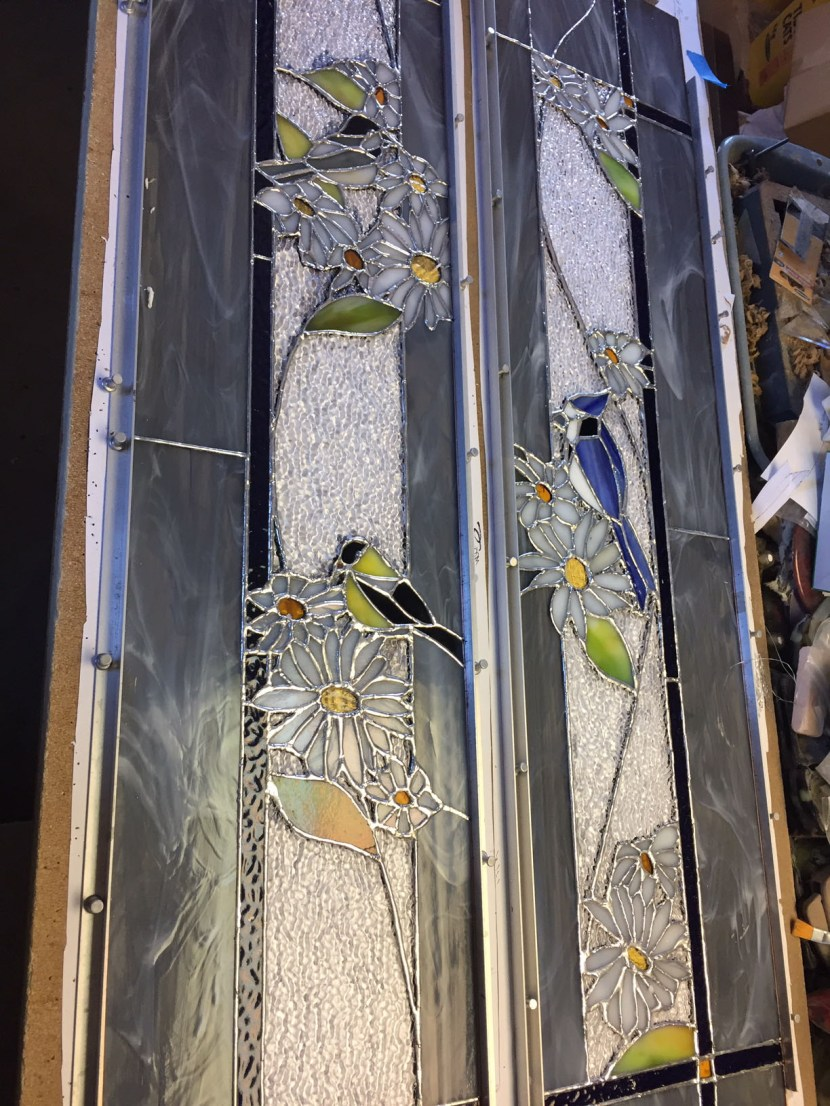 Custom stained glass sidelights soldered and ready for patina.