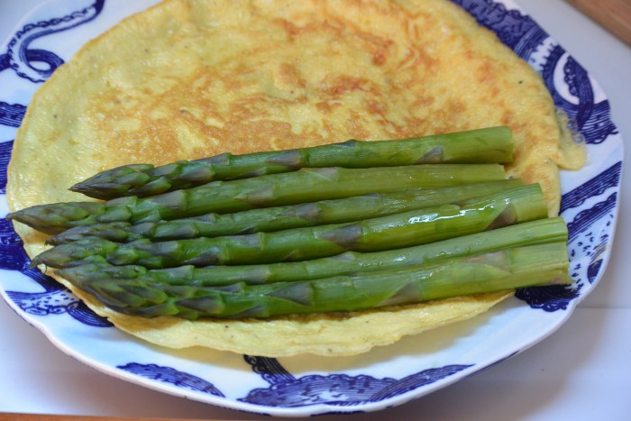 lay steamed asparagus on omelette