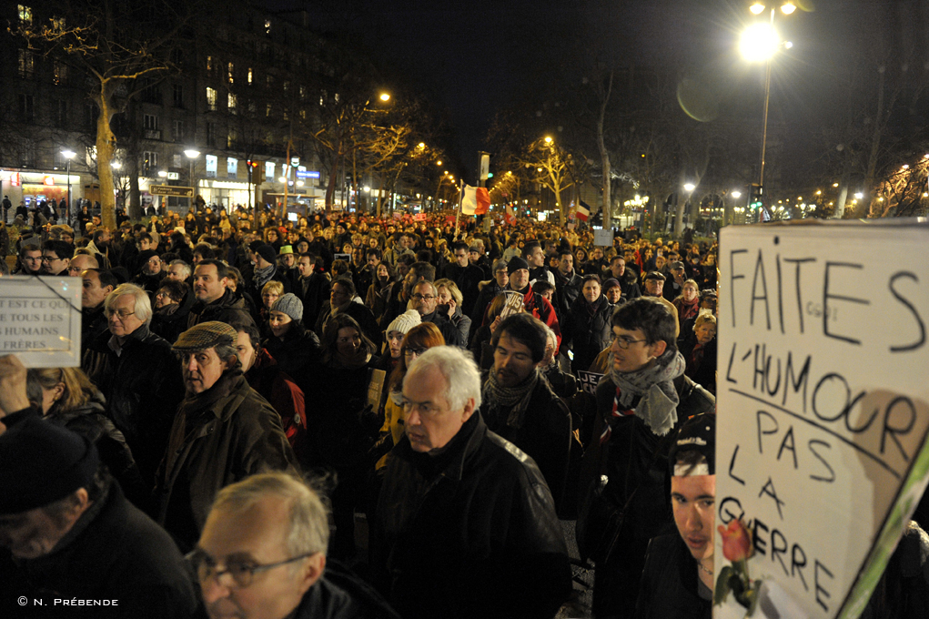 protestors in walk with signs at night