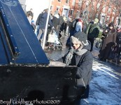 man playing piano in city center