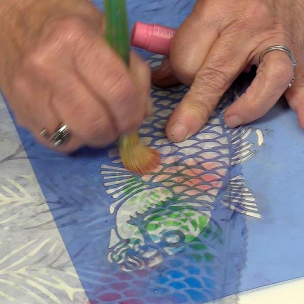Image of stenciling demonstration on batik fabric — from Cloth Doll Mermaids featuring Patti Medaris Culea