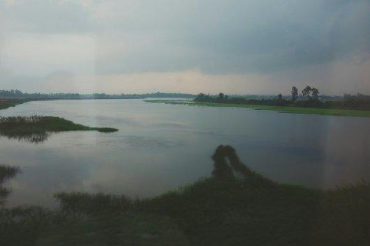 Überflutete Felder (aus dem fahrenden Zug durch die Scheibe hindurch)
