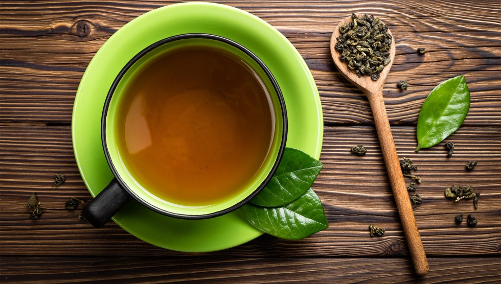 A cup of brewed green tea on a wood surface with a wood spoon and scattered green tea leaves.
