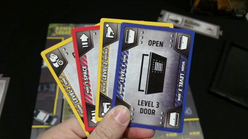 The 4 types of cards come in 3 colors. Only the correct color/action combinations will let you rescue hostages, disarm bombs, and open doors. Also, if you are holding your cards like this, you're doing it wrong.