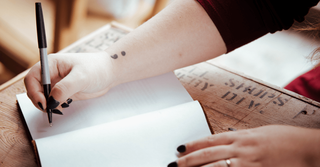 person with a semi colon tattoo and black nail polish about to write in a notebook