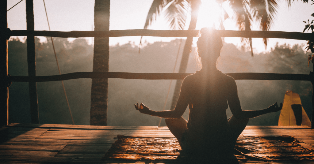 woman sitting on a deck meditating in sunlight