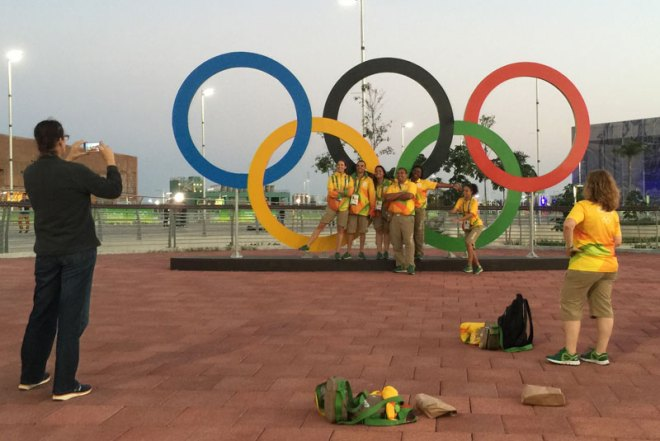 Rio 2016 volunteers take a last opportunity to pose with the Olympic Rings the evening before crowds descend on Olympic Park (GamesBids Photo)