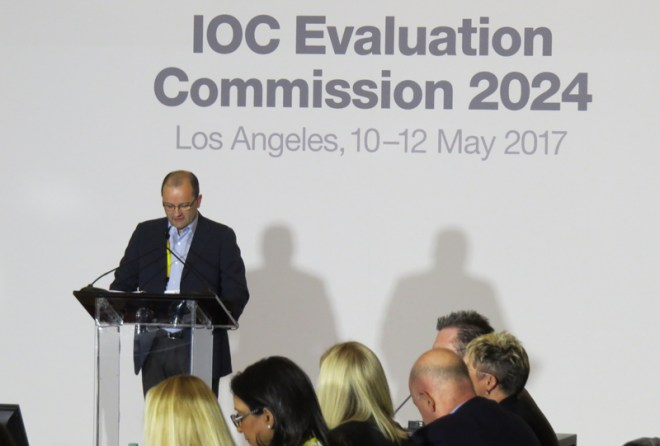 IOC 2024 Evaluation Commission Chair Patrick Baumann makes remarks at opening meeting with Commission members in foreground (GamesBids photo)