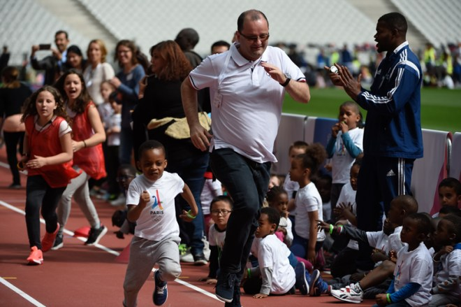 IOC 2024 Evaluation Commission Chair Patick Baumann runs with a school boy at the Stade de France in Paris on May 15 (Paris 2024 Photo)