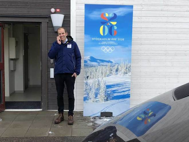 Stockholm-Åre 2026 CEO Richard Brisius stands beside bid banner at side-entrance to Lugnet Nordic Complex in Falun, Sweden March 14, 2019. It was a rare appearance of promotional material in Sweden (GamesBids Photo)