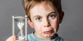 ein enttäuschter Junge mit einer sanduhr schaut grimmig, weil seine Zeit abläuft