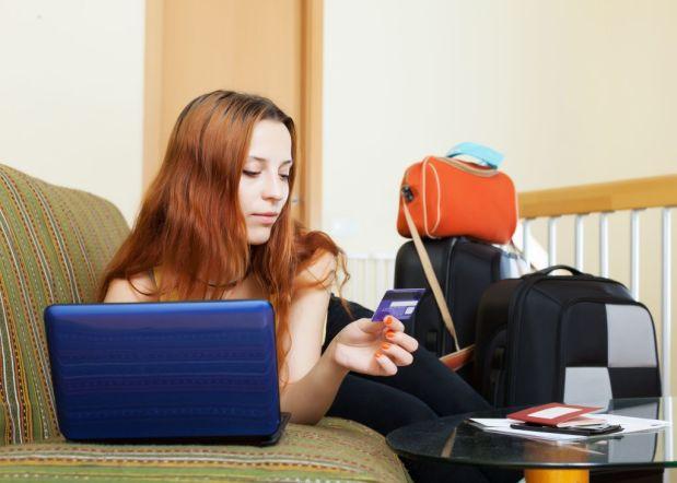 Mujer joven tumbada en su sillon con un portatil al lado y varias maletas con cosas para vender en Internet