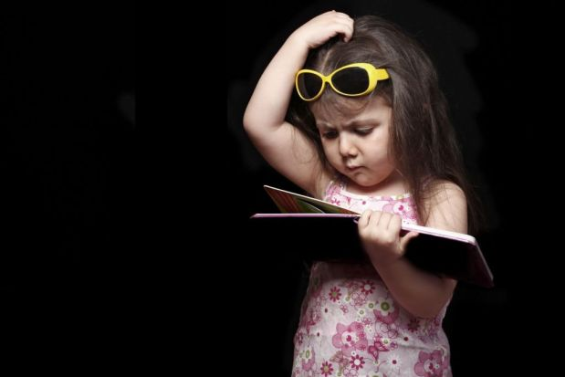 Nina con un vestido rascandose la cabeza mientras mira un libro que sostiene en su mano sobre un fondo negro