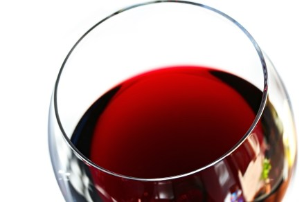 Glass of red wine, in close-up with white background. Soft focus.