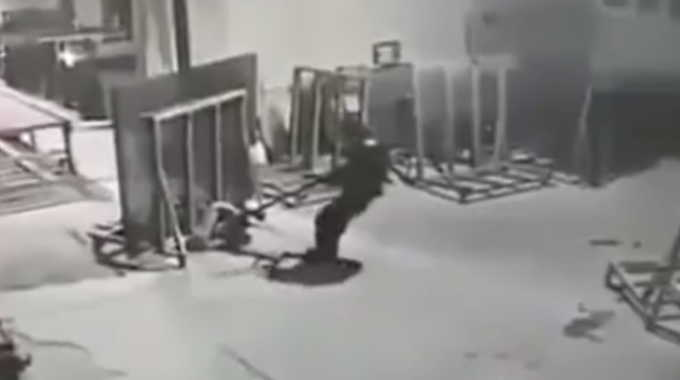 大きなステンレスの板に押し潰される中国の作業員。