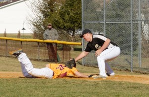 Golden Tide first-baseman Ricky Magnuson applies a late pick-off tag on ECC's Ivan Wortman in yesterday's game.  Wortman was 4-for-4 to help the Crusaders to a 3-1 win.