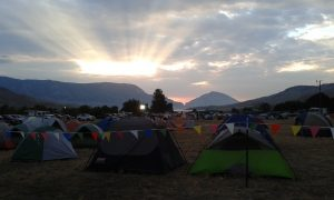The sun rises over base camp near the Buffalo Bill Reservoir in Cody, Wyo. Wildland firefighters stay in tents at the camp before heading out to their assignments on the Whit Fire. While some crews stay at the base camp, some crews will spike out in remote areas away from the main camp in order to have better access to the areas they are working in. (Photo by Kimberly Finnigan)