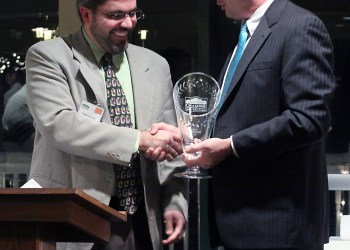 Todd Arnold receives the 2010 Community Cup from Carl Lias, Chairman of the chamber of the commerce.