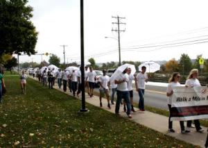 Men in high heels walk along Route 255 in front of campus during the Walk a Mile in Her Shoes event. (Provided photo)