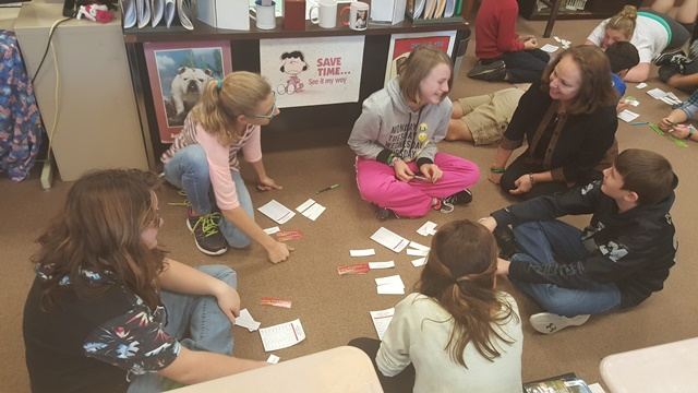 Michelle DiGilarmo helps students with an activity during a JA class. (Provided photo)