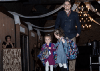 Dr. Chris Varacallo is accompanied by his daughters Leah and Cece as he walks the 2018 Free Clinic runway for Guzzo's & Co. (Provided photo)