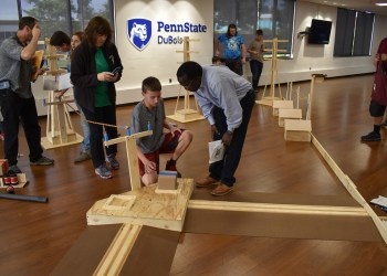 Assistant Professor of Engineering Daudi Waryoba, at center, explains to a student how robots will navigate a portion of the obstacle course for BEST Robotics 2019, during a preview of the course that teams received in the student union.  (Provided photo)