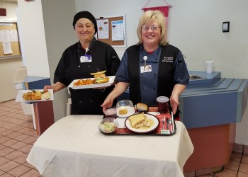 Julie Daquilante, director of food and nutrition at Penn Highlands Clearfield, left, and Mary Ann Howe, sous chef at Penn Highlands Clearfield, show off a variety of foods that are now available to patients, family and staff. Since taking the position of director of food and nutrition in May, Daquilante has worked to improve the selection of food, the service, and the kitchen facilities at the hospital. (Photo by Kimberly Finnigan)