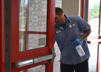 Dan Mortimer, a custodian at Cornwell Elementary School in Bensalem Township, cleans doors leading into the polling place for two precincts during Tuesday's special House district 18 election. (Emily Previti / PA Post)