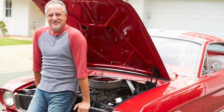 Retired Senior Man Working On Restored Classic Car Smiling To Camera