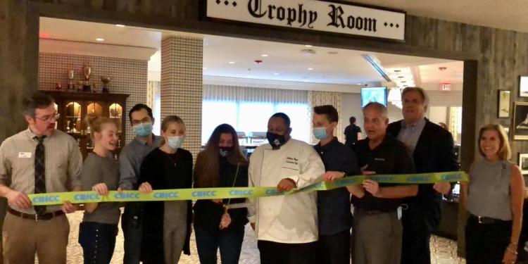 To celebrate the opening of the Trophy Room bar and restaurant at Graduate State College, Jessica Jacoby McCloskey, Director of Sales, cuts the CBICC ribbon surrounded by CBICC members and fellow team members Kyra Ebersole, Banquet Manger, Will Thomas, Chef, and Brian Walker, Bar & Restaurant Manager.