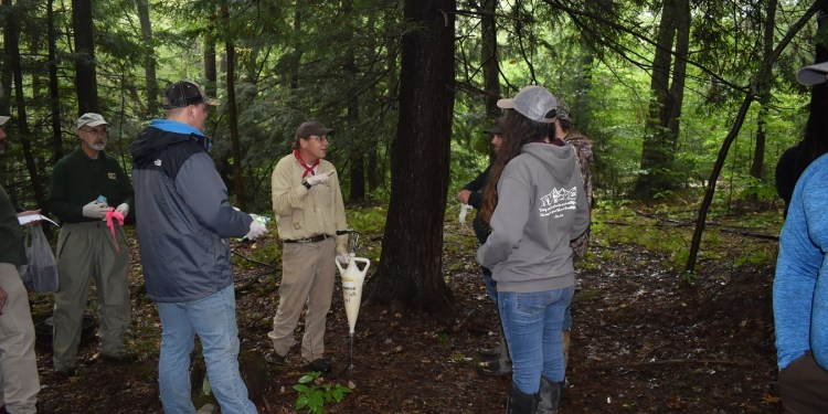 DCNR Forester Bill Laubscher, center, demonstrates the application of insecticide around the base of hemlock trees for Penn State DuBois students. The work students assisted with is intended to protect the trees from the hemlock woolly adelgid, an invasive insect that poses a serious threat to Pennsylvania's state tree.