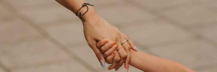 unrecognizable mother holding hands with daughter