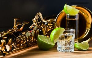 Image of saxophone and tequila with lime on wooden table