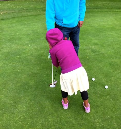 Image of little girl and her dad on the putting green trying to putt the ball into the hole