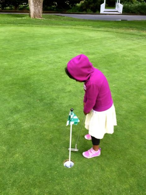 Image of little girl putting a ball at the golf course