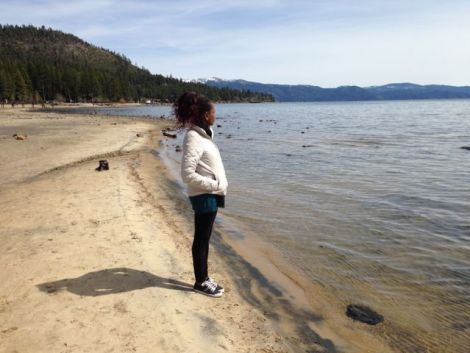 Woman standing on Lake Tahoe beach looking out into the mountains.