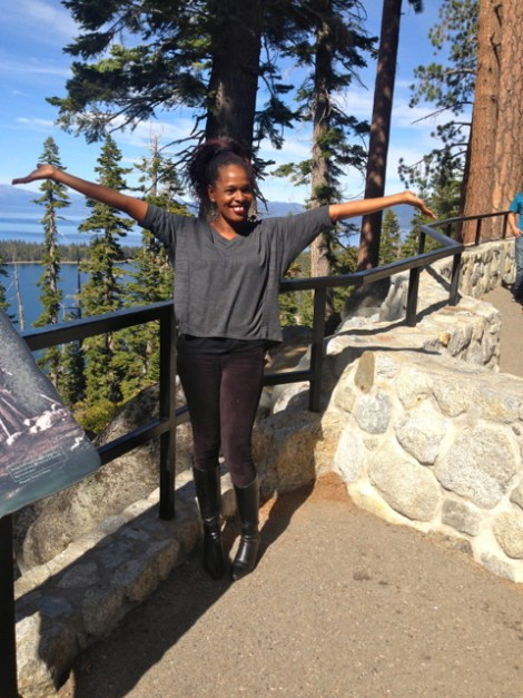 Woman in a celebratory pose standing in front of Emerald Bay!