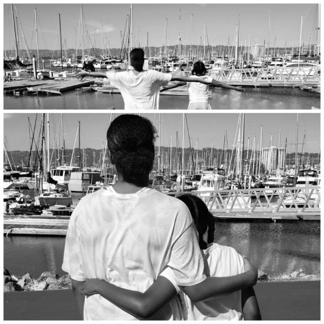 Image of two African American girls looking out into a Lake with boats docked on it.