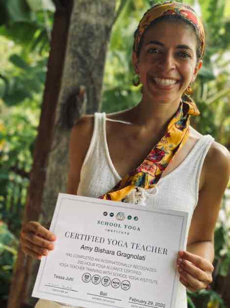 Image of beautiful woman holding up her Yoga Teacher Certification