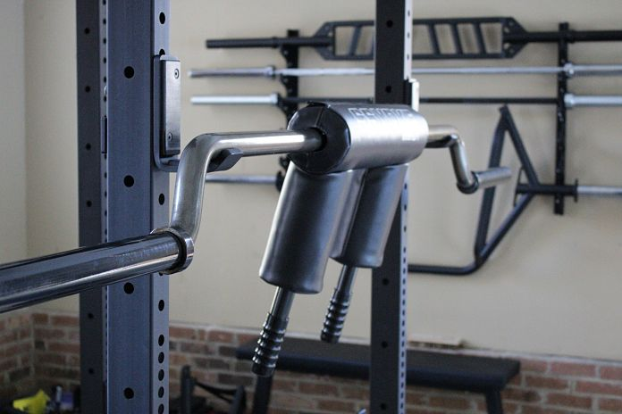 EliteFTS Safety Squat Bar in Garage Gym with Gun Rack in Back