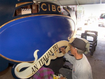 Rick Bendi swinging a brush on this carved sign.