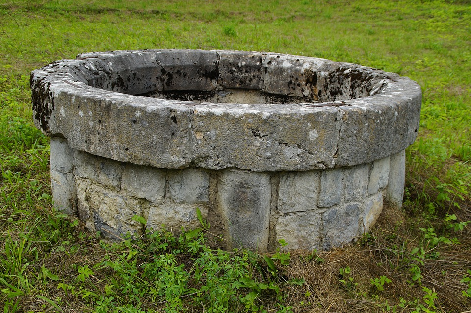 An ancient cistern made of stone and mortor in the middle of a green field of grass.