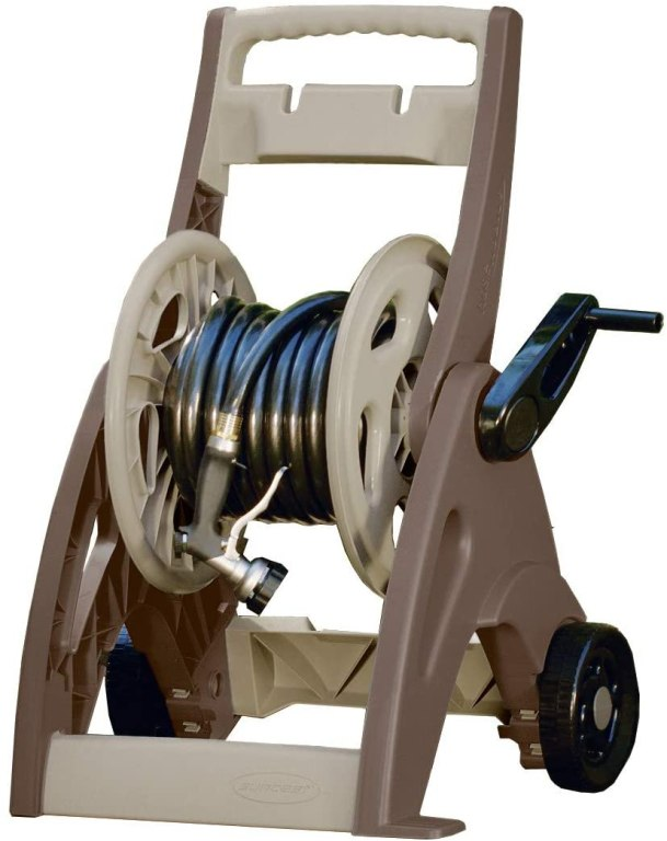 A tan garden hose reel with black handle and wheels.