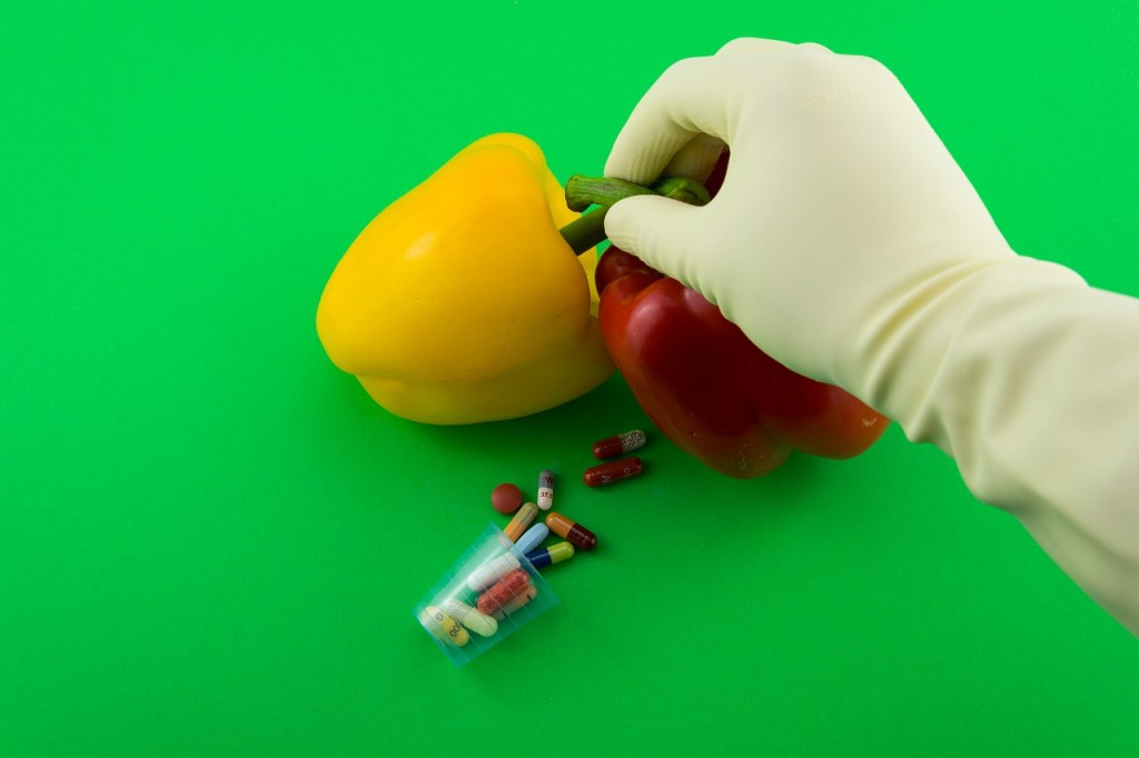 A gloved-hand ties two peppers together, and a vile of pills lies nearby.