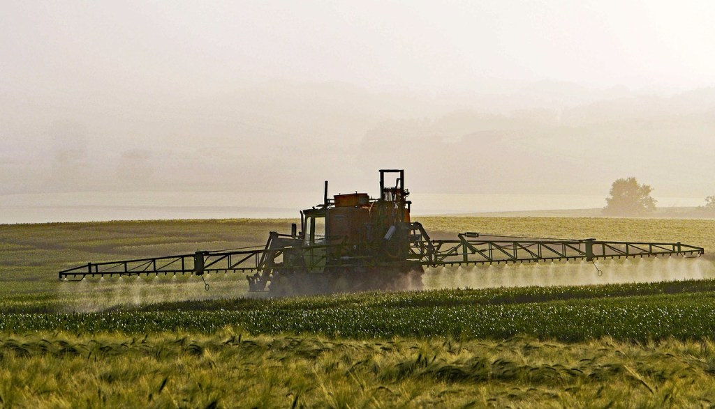A large piece of farm equiptment spraying pesticides over crops on an industrial scale.